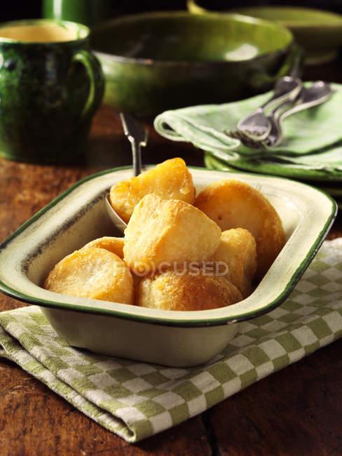Dourado assado batatas no prato vintage, mesa de madeira — Fotografia de Stock