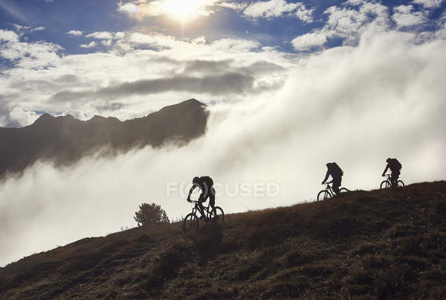 Tre persone in mountain bike, Vallese, Svizzera — Foto stock