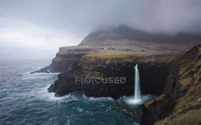 Cascata sulla costa rocciosa — Foto stock