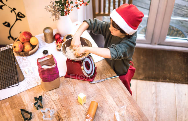 Ragazzo che pesa la farina in scala a casa — Foto stock