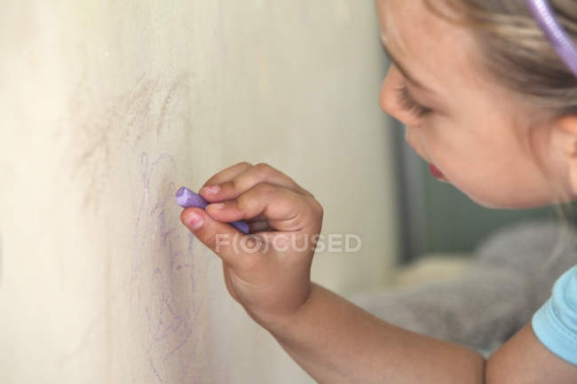 Little girl drawing on wall with chalk — стокове фото