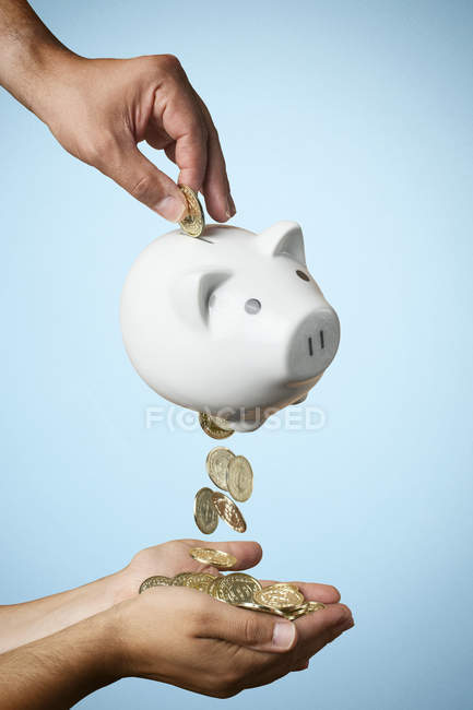 Closeup Aufnahme von Hand, Münze ins Sparschwein und Münzen heraus fließt auf farbigem Hintergrund — Stockfoto