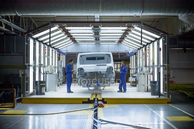 Lavoratori e veicoli nella stazione di ispezione nella fabbrica di automobili — Foto stock