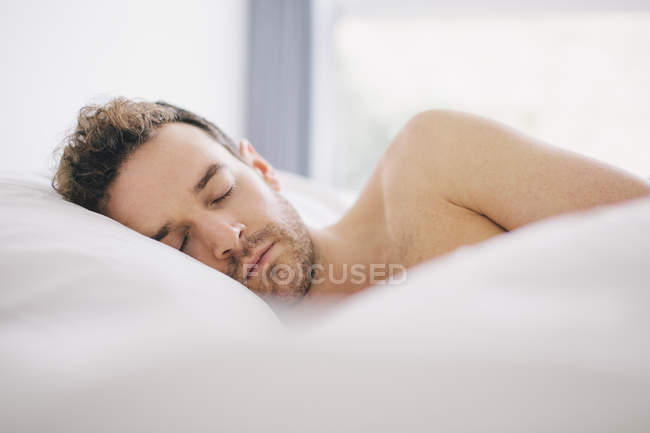 Young man lying on side asleep in bed — Stock Photo