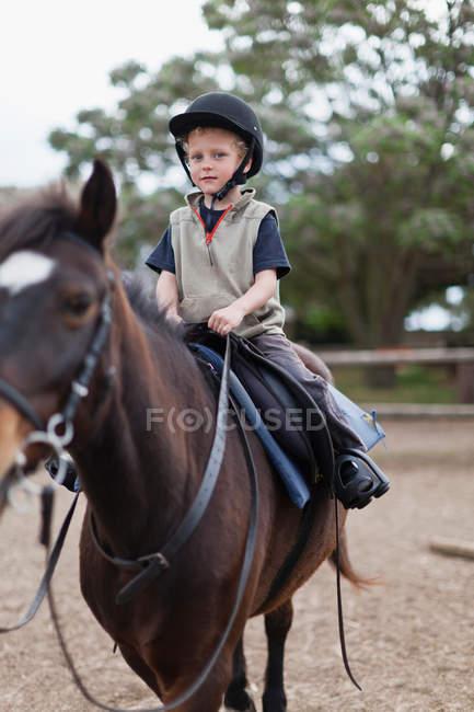 Menino equitação cavalo no quintal, foco seletivo — Fotografia de Stock