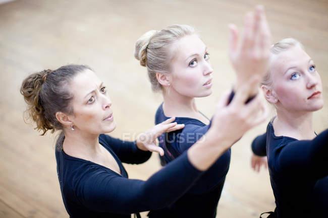 Учитель, демонстрирующий ручную позу балеринам — стоковое фото