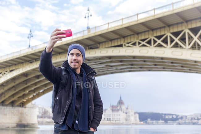 Visão de baixo ângulo do jovem na frente da ponte Margaret usando smartphone para tirar selfie sorrindo, Budapeste, Hungria — Fotografia de Stock