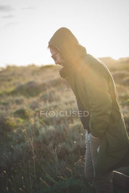 Hombre adulto medio paseando en campo iluminado - foto de stock