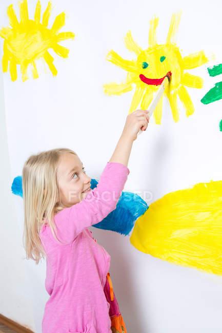 Молодая девушка рисует улыбающееся солнце на стене — стоковое фото