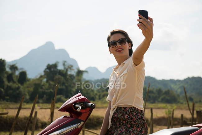Жінка фотографує самоврядування на мопеда, Ванг Макао, Лаос — стокове фото