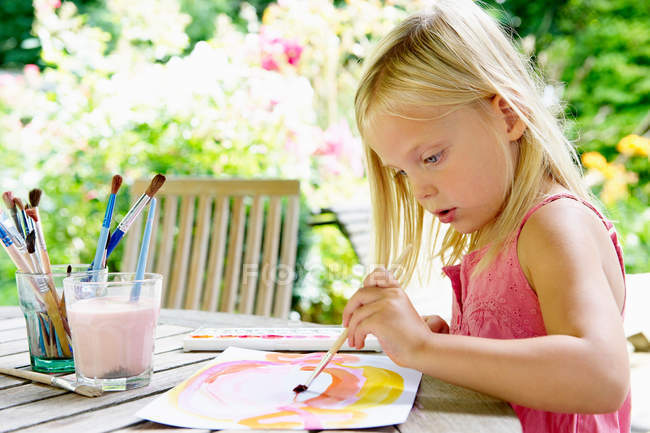 Small Girl painting with paintbrush outdoors — Stock Photo