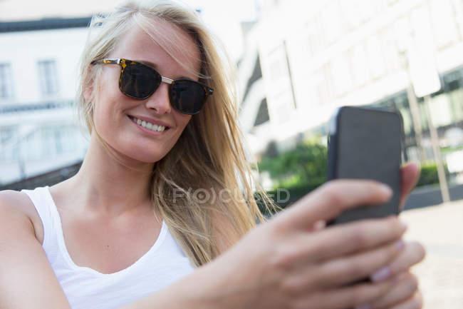 Giovane donna che usando il telefono cellulare — Foto stock