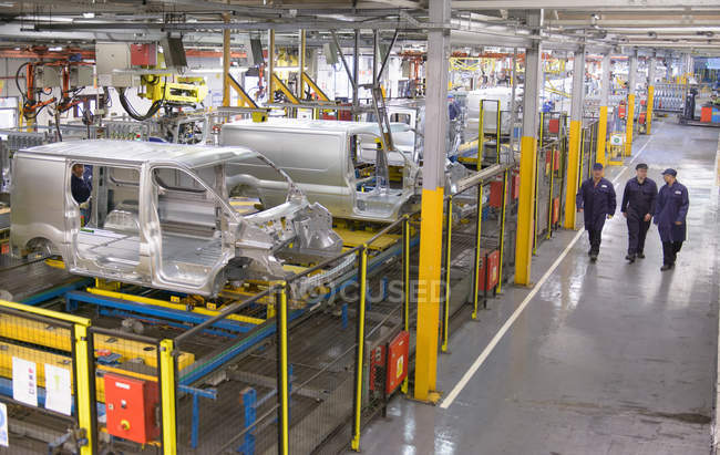 Высокий угол обзора автомобильных рабочих, идущих на автомобильном заводе — стоковое фото