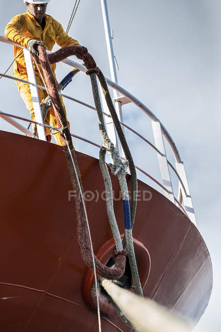 Worker pulling up ropes on oil tanker deck — Stock Photo