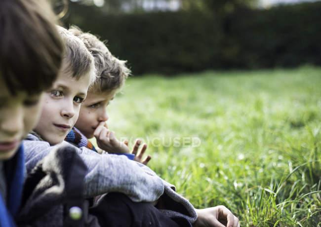 Três meninos, sentados juntos no campo, no outono — Fotografia de Stock