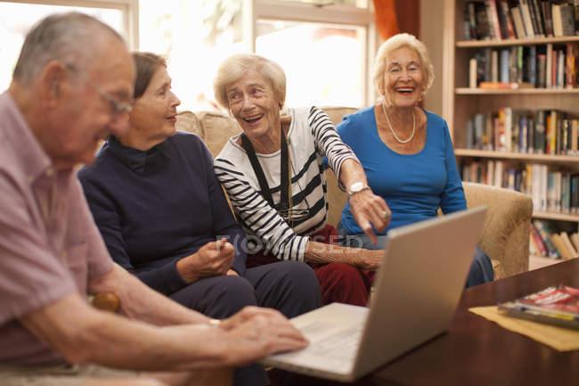 Seniorinnen und Senioren mit Laptop in Rentnervilla — Stockfoto
