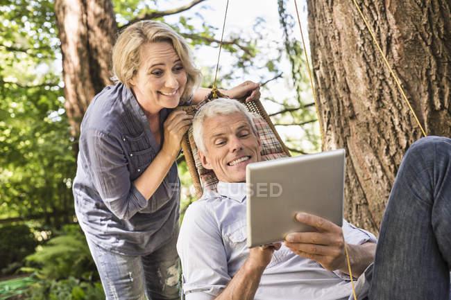 Frau beobachtet Ehemann mit digitalem Tablet auf Hängematte — Stockfoto