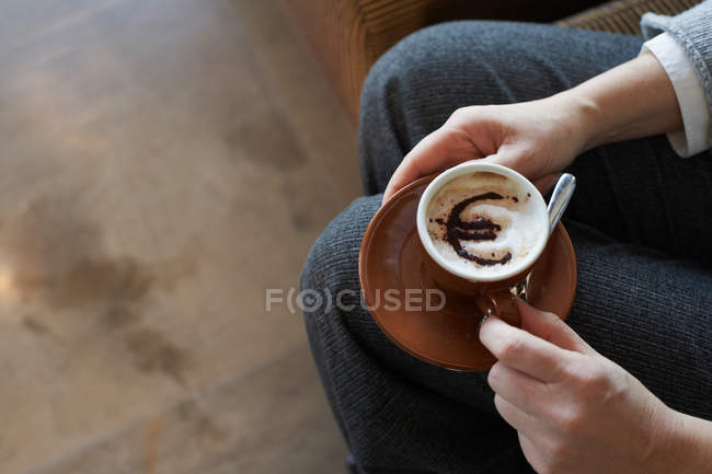 Woman holding cappuccino with euro motif — Stock Photo