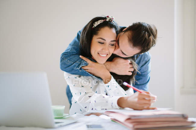 Young man hugging girlfriend working at home on laptop — Stock Photo