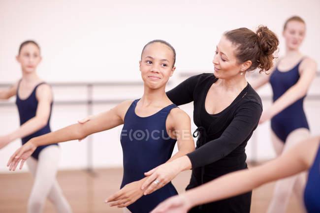Teacher adjusting arms of ballerina — Stock Photo