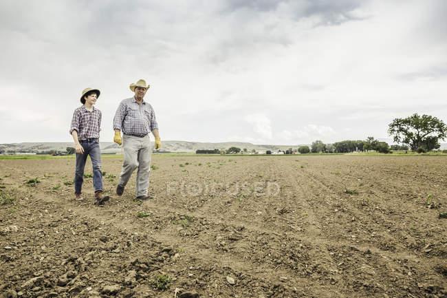 Agriculteur et adolescent marchant sur champ labouré — Photo de stock