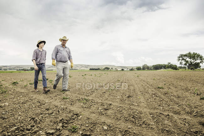 Male farmer and teenage boy walking over ploughed field — Stock Photo