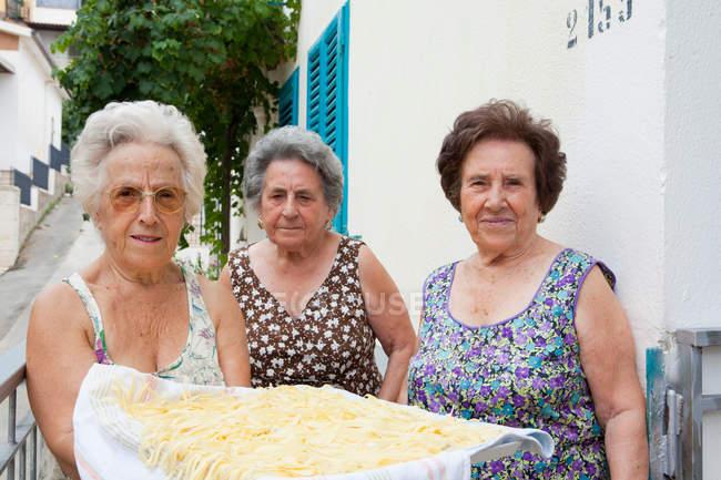 Donne anziane con cesto di pasta, attenzione al primo piano — Foto stock