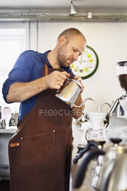 Barista mâle versant l'eau bouillante dans le filtre de café — Photo de stock