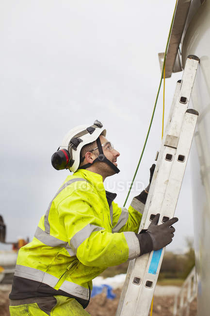 Engineer climbing ladder while working on wind turbine construction site — Stock Photo