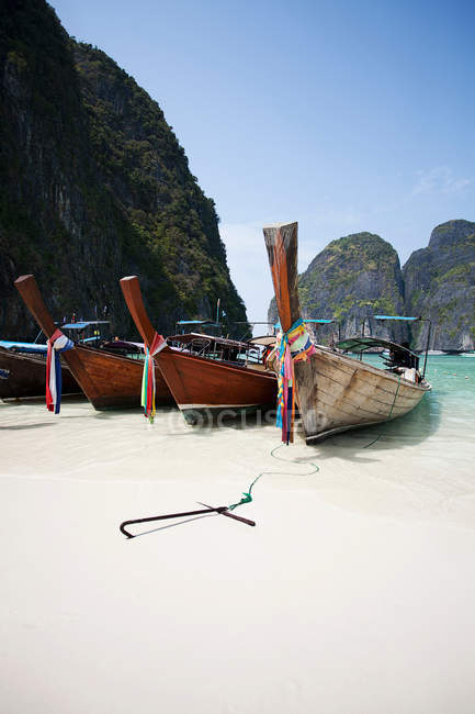 Boats docked on sandy beach with rocks on background — Stock Photo