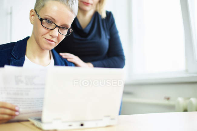 Businesswoman with paperwork and colleague hand on shoulder — Stock Photo