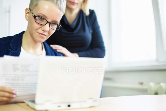 Деловая женщина с бумажной работой и коллега рука об руку — стоковое фото