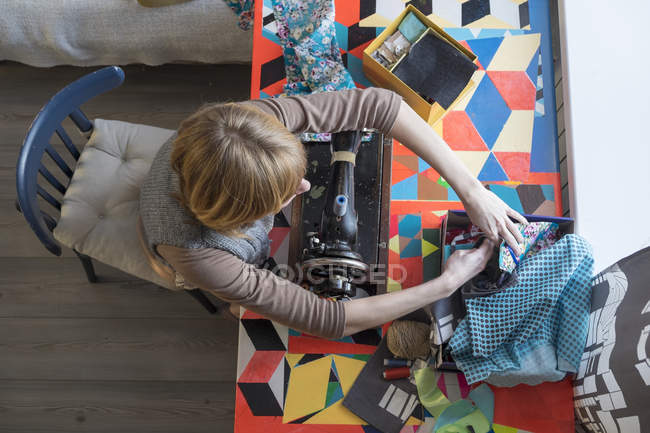 Overhead view of woman with vintage sewing machine selecting fabric — Stock Photo