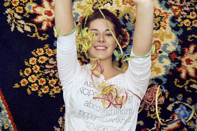Portrait of young woman and streamers lying on patterned rug — Stock Photo
