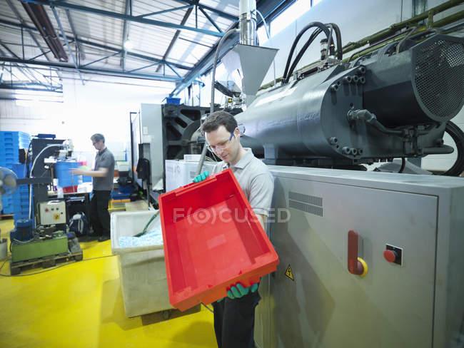 Travailleur inspectant des caisses en plastique dans une usine de plastique — Photo de stock