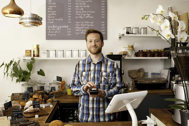 Portrait of cafe waiter with card machine behind counter — Stock Photo