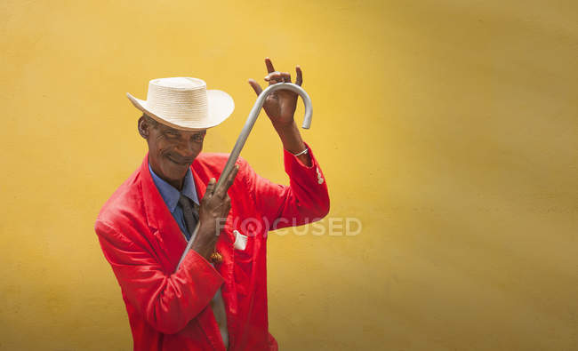 Mature male dancer poised in front of yellow wall, Havana, Cuba — Stockfoto