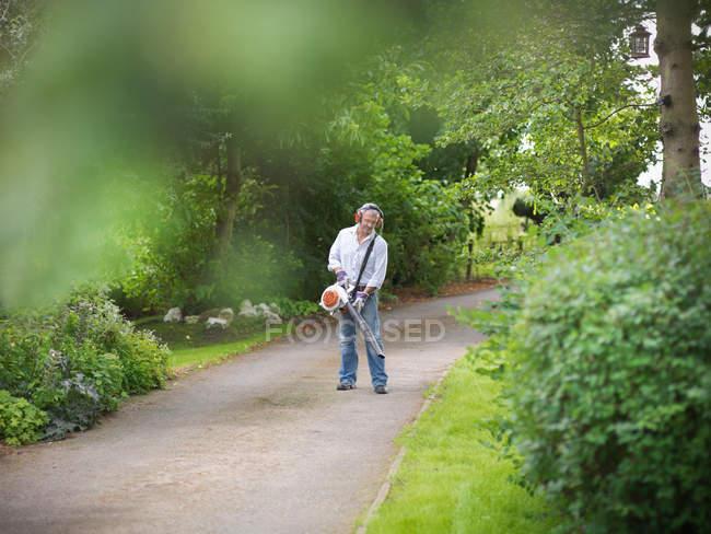 Садівник носіння вухо захисників і козирок, використовуючи лист вентилятор шлях — стокове фото