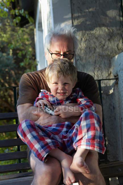 Старший мужчина обнимает внука на улице — стоковое фото