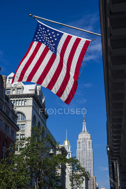 View of American flag and the Empire State Building from fifth avenue, New York, USA — Stock Photo
