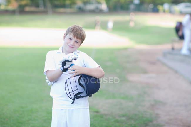 Портрет хлопчика в крикет рукавичках і проведення шолом — стокове фото