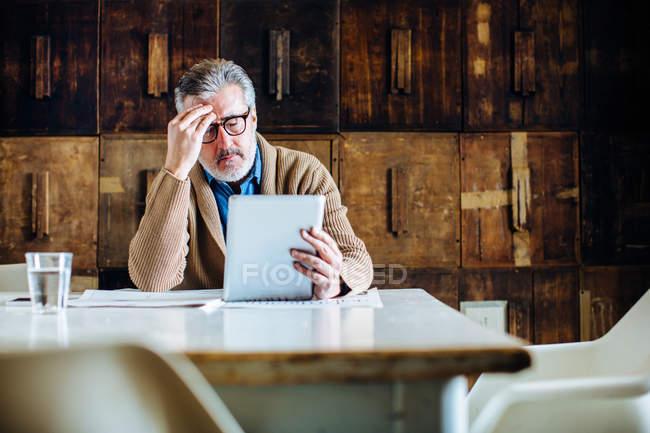 Homem maduro com a mão na testa leitura digital tablet na mesa de jantar — Fotografia de Stock