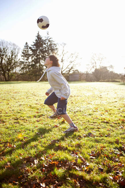 Boy playing with soccer ball in meadow — Stock Photo