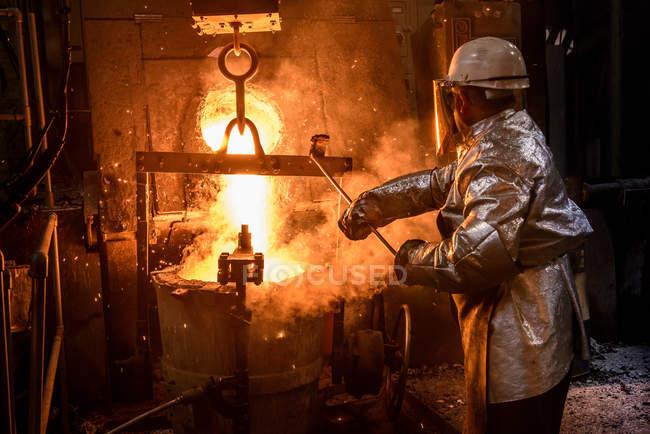Trabalhador derramando metal fundido na fundição, visão traseira — Fotografia de Stock