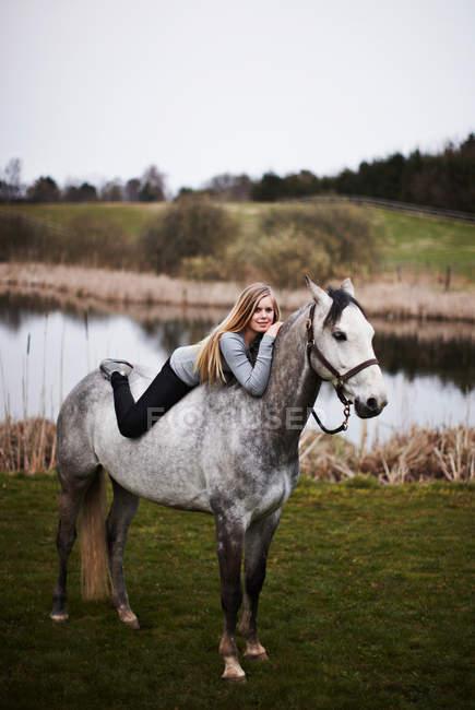 Menina que coloca no cavalo no campo — Fotografia de Stock