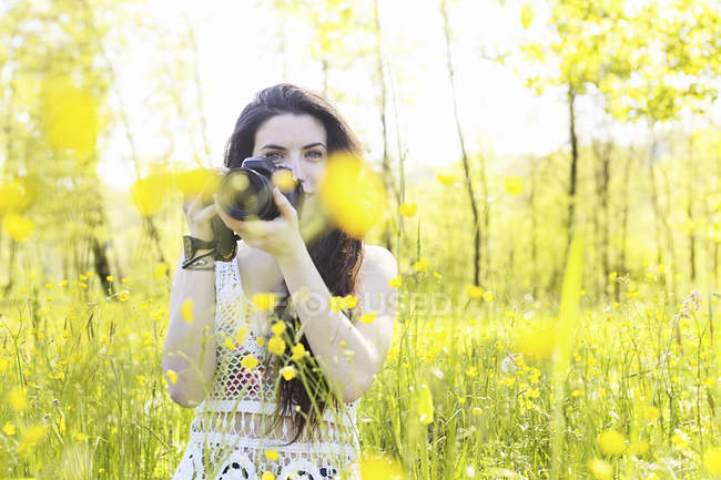 Young woman holding camera in flowery field — Stock Photo