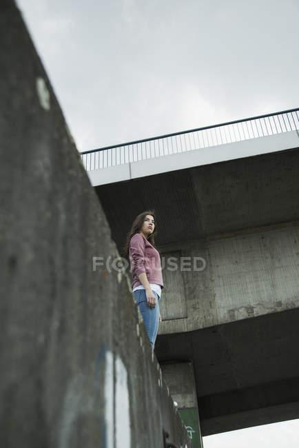Mujer joven de pie en la pared, ángulo bajo - foto de stock