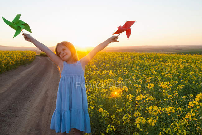 Girl playing with pinwheels outdoors — Stock Photo