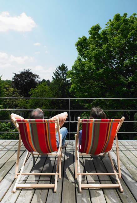 Visão traseira do casal desfrutando de sol em poltronas — Fotografia de Stock