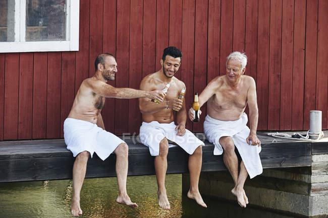 Tre uomini seduti con birra fuori sauna — Foto stock